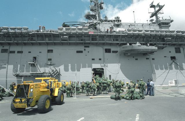 An M4K forklift, one of many pieces of equipment from the 25th Infantry Division being prepared for transport, stands on the pier as troops board the amphibious assault ship USS BELLEAU WOOD (LHA-3). Troops and equipment are being transported to the island of Kauai as part of Task Force Garden Isle, a joint military disaster relief effort being conducted in the aftermath of Hurricane Iniki
