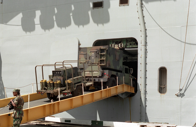 An M998 High-Mobility Multipurpose Wheeled Vehicle (HMMWV), with shelter attached and pulling a generator, is driven aboard the amphibious assault ship USS BELLEAU WOOD (LHA-3). The vessel is transporting equipment of the 25th Infantry Division to the island of Kauai as part of Task Force Garden Isle, a joint military disaster relief effort being conducted in the aftermath of Hurricane Iniki