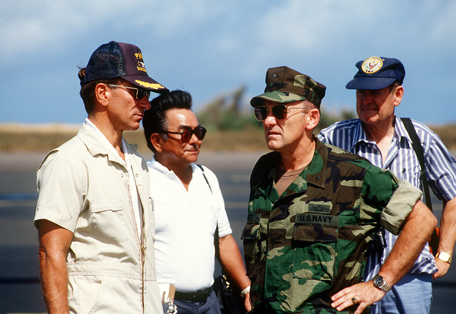 Military and civilian officials discuss damage to the Pacific Missile Range Facility (PMRF), Kauai, in the aftermath of Hurricane Iniki. Pictured, from left, are: CAPT. Robert Mullens, commanding officer, PMRF; John Mihara, Naval Facilities Engineering Command, Pacific Division; Rear Adm. (lower half) William Retz, commander, Naval Base, Pearl Harbor, and an unidentified official from the Federal Emergency Management Agency