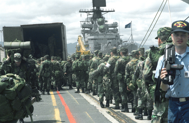 Soldiers of the 25th Infantry Division assemble on the pier as they prepare to board the amphibious assault ship USS BELLEAU WOOD (LHA-3) for transport to the island of Kauai as part of Task Force Garden Isle, a joint military disaster relief effort being conducted in the aftermath of Hurricane Iniki