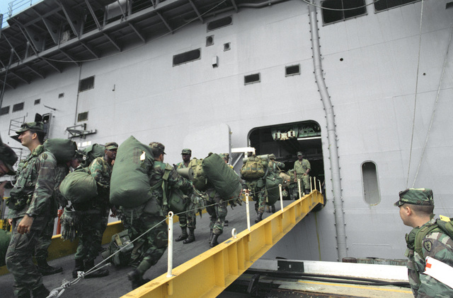 Troops of the 25th Infantry Division assemble on the pier as they prepare to board the amphibious assault ship USS BELLEAU WOOD (LHA-3) for transportation to the island of Kauai. Equipment and troops are being transported to the region to take part in Operation Garden Isle disaster relief efforts in the aftermath of Hurricane Iniki