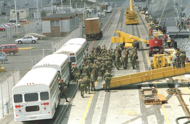 Troops of the 25th Infantry Division assemble on the pier as they prepare to board the amphibious assault ship USS BELLEAU WOOD (LHA-3) for transport to Kauai as part of Task Force Garden Isle, a joint military disaster relief effort being conducted in the aftermath of Hurricane Iniki