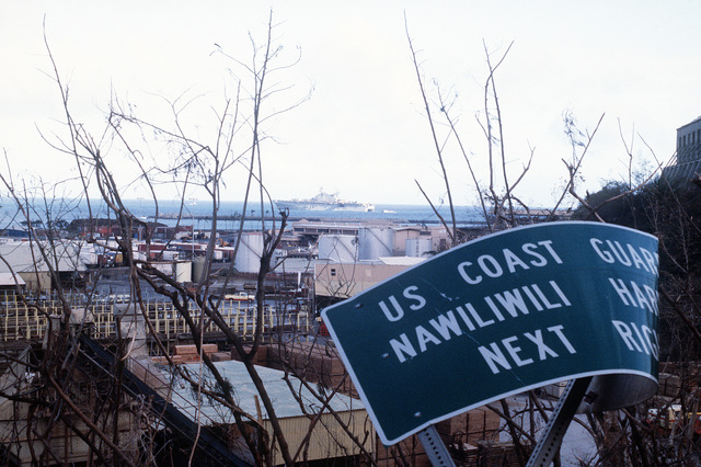 A damaged sign in the foreground is a minor example of destruction caused by Hurricane Iniki when it struck the island of Kauai. The amphibious assault ship USS BELLEAU WOOD (LHA-3) is anchored in the harbor, background, as landing craft and helicopters deliver supplies from the vessel to residents of Kauai as part of Joint Task Force Garden Isle, a joint military disaster relief effort