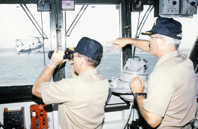 RADM William Retz, commander, Naval Base, Pearl Harbor, and CAPT Douglas Bradt, commanding officer of the amphibious assault ship USS BELLEAU WOOD (LHA-3), watch from the ship's bridge as supplies are unloaded from the vessel by members of Joint Task Force Garden Isle. The task force was organized to provide disaster relief for residents of the area in the aftermath of Hurricane Iniki
