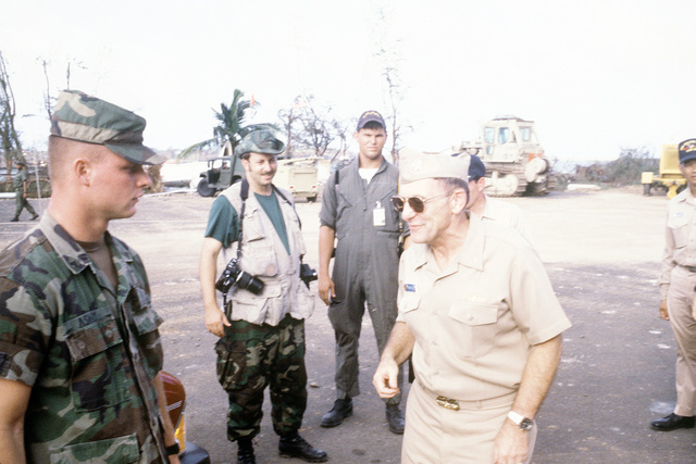 RADM William Retz, commander, Naval Base, Pearl Harbor, converses with a soldier who is assisting in transporting supplies by landing craft from the amphibious assault ship USS BELLEAU WOOD (LHA-3) to the island of Iauai. The delivery is part of Joint Task Force Garden Isle, a joint military disaster relief effort which was organized to provide assistance to the residents of the region in the aftermath of Hurricane Iniki
