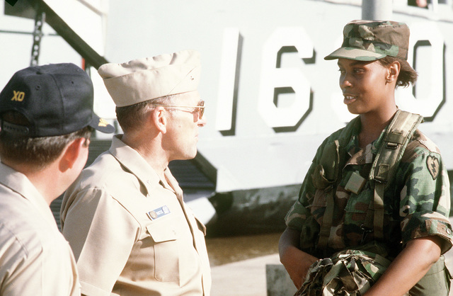 RADM William Retz, commander, Naval Base, Pearl Harbor, speaks with a soldier as CAPT Robert Annis, executive officer of the amphibious assault ship USS BELLEAU WOOD (LHA-3), stands by during the unloading of supplies from the BELLEAU WOOD. Members of the Joint Task Force Garden Isle are taking part in the supply delivery to assist residents of Kauai and surrounding areas in the aftermath of Hurricane Iniki