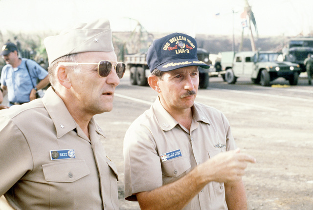 RADM William Retz, commander, Naval Base, Pearl Harbor, speaks with CAPT Robert Annis, executive officer of the amphibious assault ship USS BELLEAU WOOD (LHA-3), as the two watch supplies being unloaded from the BELLEAU WOOD. The supply delivery is part of Joint Task Force Garden Isle, a joint military disaster relief effort organized to assist the residents of Kauai and surrounding areas in the aftermath of Hurricane Iniki