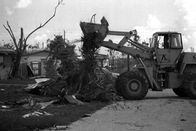 A soldier from the 46th Engineers, Fort Rucker, Alabama, uses a front end loader to remove debris left behind near Culter Ridge by Hurricane Andrew