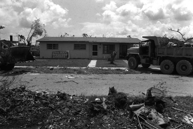 Soldiers from the 46th Engineer Battalion, Fort Rucker, Alabama, use a front end loader and a dump truck to remove debris, in front of an insurance company, created by Hurricane Andrew near the base
