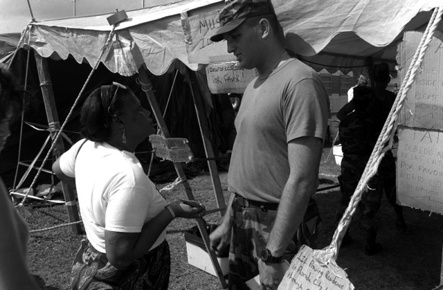 PVT Robert W. Hopkins from HHC 1/87th Infantry Regiment checks identification cards of local residents whose possessions were lost as a result of Hurricane Andrew