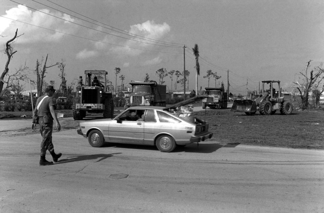 SGT Phillip Shaffer directs traffic while vehicles transport debris from a small town near Homestead Air Force Base after Hurricane Andrew wreaked havoc