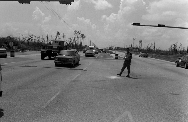 SPC Mike Armstead from the 437th Military Police Company, Fort Belvoir, Virginia, helps direct traffic after Hurricane Andrew knocked out power to the area
