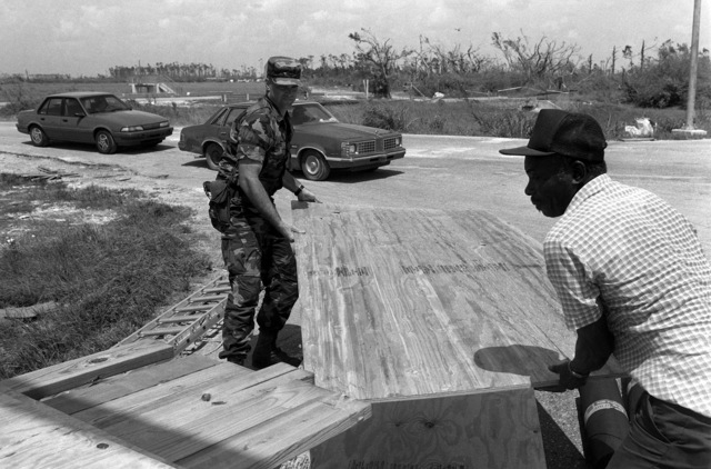 SPC Phillip Hyyit from the 437th Military Police Company, Fort Belvoir, Virginia, helps a local civilian stack plywood that will be transported to the victims of Hurricane Andrew