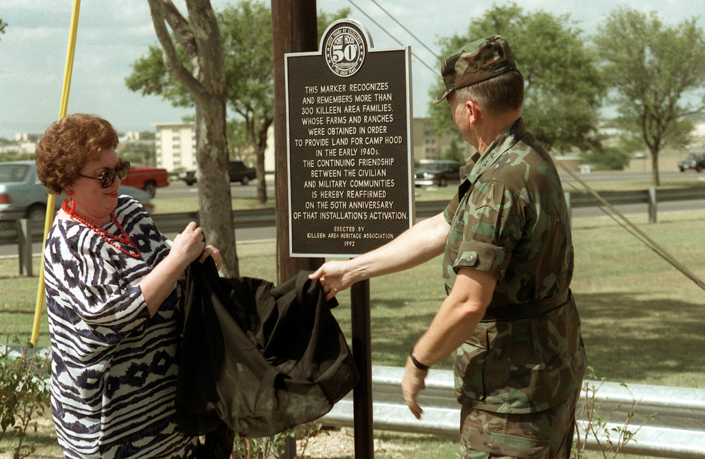 Mrs. Annette Lucksinger, President, Killeen Area Heritage Association, and Lieutenant General Horace G. Taylor, Commander III Corps and Fort Hood unveiling a commemorative marker, recognizing the 300 or more families whose land was obtained in order to provide land to Fort Hood. The marker was a tribute to Fort Hood's 50th Anniversary