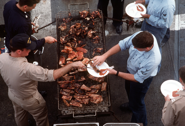 Crew members enjoy a barbeque during a steel beach picnic aboard the guided missile frigate USS MCCLUSKY (FFG-41) as the vessel is underway en route to Vladivostok, Russia for a port visit
