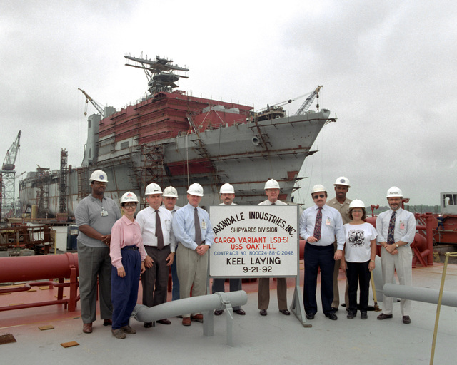 Officials of Avondale Industries, Shipyards Division, and U.S. Navy officials pose for a photograph following the keel lay ing of the dock landing ship OAK HILL (LSD-51), which took place on September 21st. They include, from left: H. Brown, SSNO, asst. hull mgr.; M. Garza, production dept.; M. Lusick, NAVESA, acquisition mgr. (PMS 377G); E. Foret, vice-pres., ship construction; G. Smith, NAVESA, asst. acquisition mgr. (PMS377G); S. Pearce, proj. engineering coord.; G.J. Griffin, proj. eng.; D. Gordon, prog. mgr.; LT. I. Pierce, SSNO, hull mgr.; S. Punch, prog. sec. and C. Agregaard, asst. prog. mgr