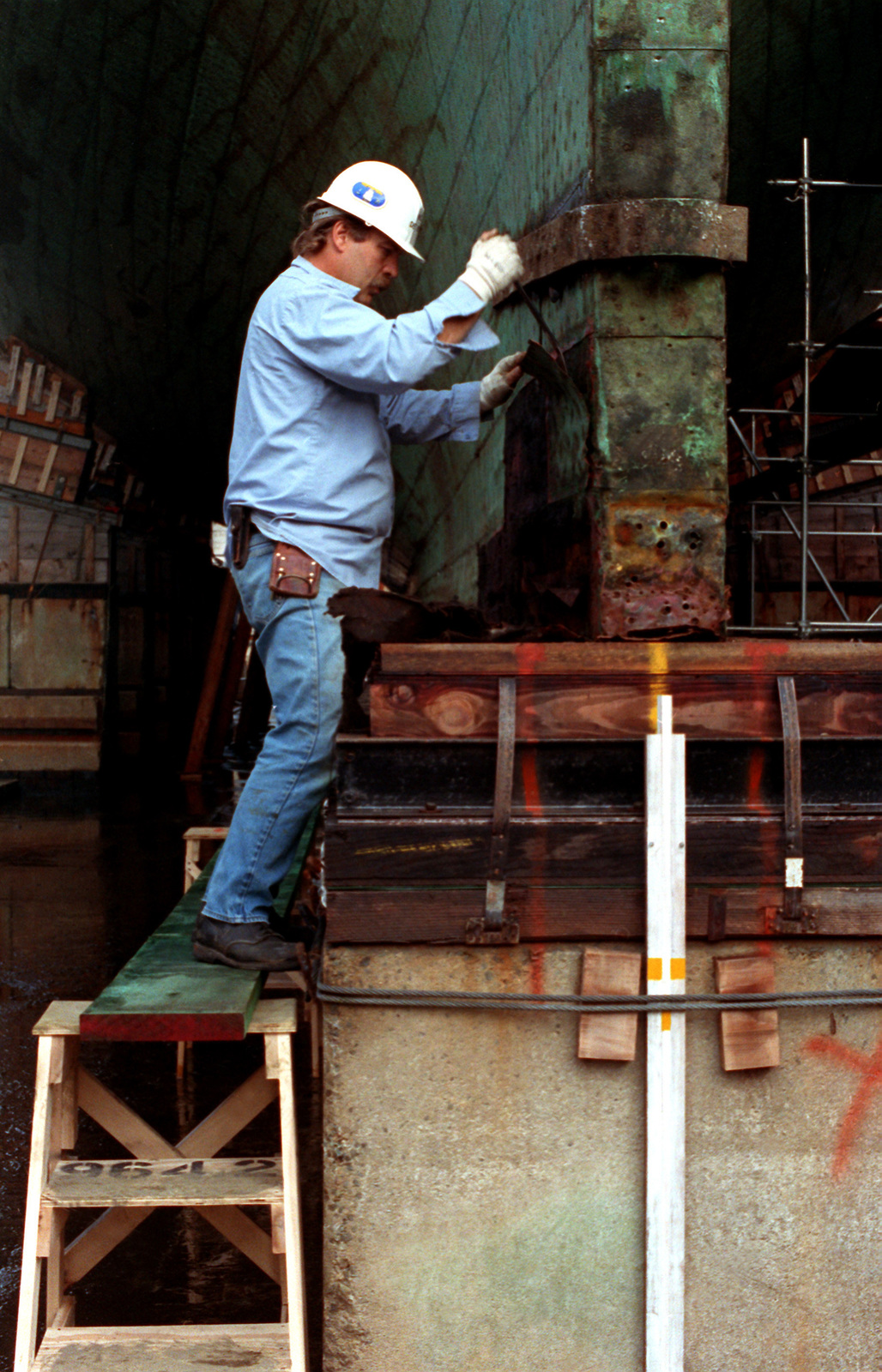 A worker removes some of the copper sheathing from the sternpost of the 44-gun sail frigate USS CONSTITUTION in a dry dock at the Charleston Memorial Shipyard. The ship is being prepared for its bicentennial celebration in 1997-1998. The CONSTITUTION was launched on October 21, 1797, and is the oldest ship remaining on the Navy List. The ship's rudder has been removed
