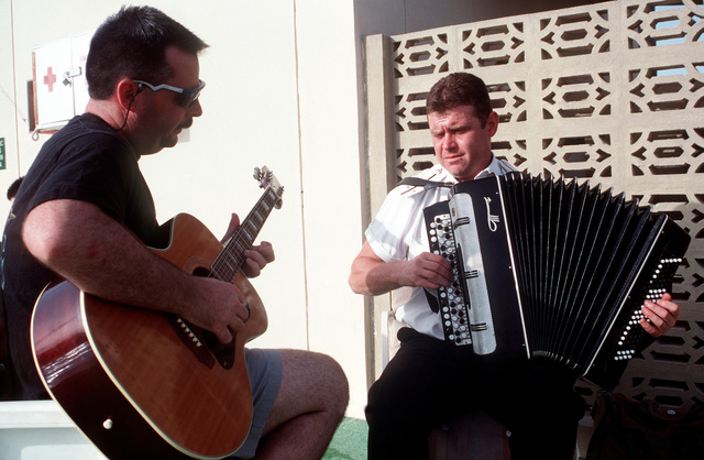 A Russian naval officer plays the accordion accompanied on guitar by a U.S. serviceman. They are attending a party hosted by the USS KINKAID (DD-965) for members of various coalition navies taking part in coalition efforts to enforce United Nations sanctions against Iraq during Operation Southern Watch