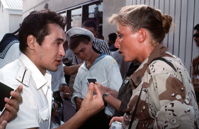 Journalist 1ST Class Sharie Derrickson speaks with a Russian officer from the guided missile destroyer ADMIRAL VINOGRADOV. The two are attending a party hosted by the USS KINKAID (DD-965) for members of the various navies taking part in coalition efforts to enforce United Nations sanctions against Iraq during Operation Southern Watch