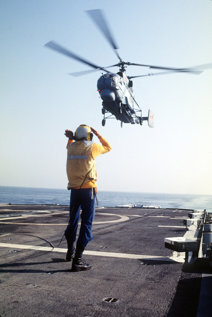 A crew member aboard the destroyer USS KINKAID (DD-965) signals to the pilot of a Russian KA-27 Helix helicopter as it prepares to land on the KINKAID's helicopter pad. The Helix is landing aboard the vessel as part of an exchange visit between helicopters from the KINKAID and the Russian destroyer ADMIRAL VINOGRADOV (BPK-554)