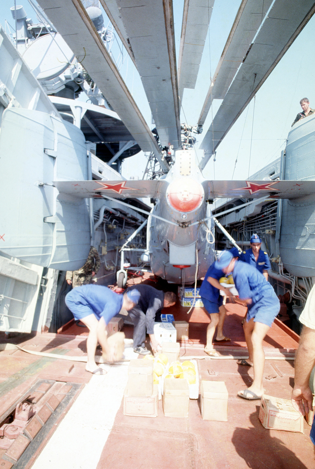 Russian sailors into the hangar bay aboard the Russian guided missile destroyer ADMIRAL VINOGRADOV (BPK-554) following the cargo's delivery by helicopter during the first Russian/U.S. Navy underway replenishment operation