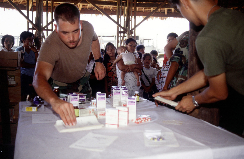 "A U.S. Army soldier from the 426th Civil Affairs, Upland, CA, prepares a myriad of medicines for nearby villagers during OPERATION BALIKATAN '92, the 12th year U.S. Army and Filipino service members have worked side by side to ""shoulder the load together,"" the Tagalog interpretation of ""balikatan."" Medical as well as other aid such as engineering and construction is given the Filipino villagers"