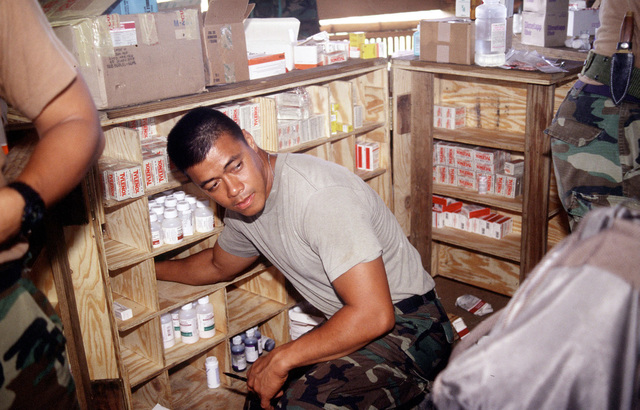 "A U.S. Army soldier from the 426th Civil Affairs, Upland, CA, reaches for a prescription to give to medical personnel who are giving aid to nearby villagers during OPERATION BALIKATAN '92, the 12th year U.S. Army and Filipino service members have worked side by side to ""shoulder the load together,"" the Tagalog interpretation of ""balikatan."" Medical as well as other aid such as engineering and construction is given the Filipino villagers"