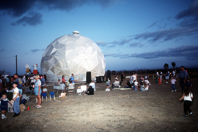 "Local children and their parents camp out beside a satellite communications done as they await the beginning of the station's annual Halloween event. During the festivities, the done is lighted and decorated to represent the ""Great Pumpkin"", a fictional character from Charles M. Schulz's ""Charlie Brown"" cartoon series"