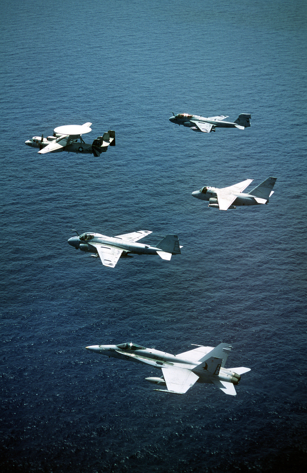 A group of aircraft assigned to the nuclear-powered aircraft carrier USS GEORGE WASHINGTON (CVN-73) fly in formation. The aircraft are an E-2C Hawkeye, an EA-6B Prowler, an A-6E Intruder, an S-3 Viking and an F/A-18C Hornet