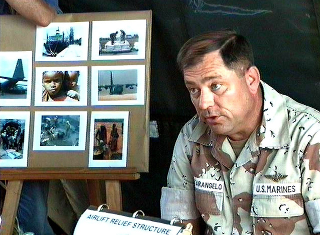 Left side front view from the chest up of US Marine BGEN Fratarangelo, Commanding General of Joint Task Force Provide Relief as he briefs international film star Sophia Loren (not shown) on the operation of airlifting food into Somalia. An easel with pictures of the relief effort is in the background to the left. This mission is in direct support of Operation Restore Hope