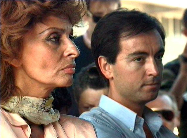 Right side profile of international film star Sophia Loren. She's visiting Joint Task Force Provide Relief facilities at Moi International Airport, Mombasa, Kenya. Ms. Loren, Goodwill Ambassador for United Nations and High Commissioner for Refugees, was briefed by US Marine BGEN Fratarangelo, Commanding General of Joint Task Force Provide Relief (not shown), on the operation that has been airlifting food into Somalia. A member of Ms. Loren's entourage is at the right. This mission is in direct support of Operation Restore Hope