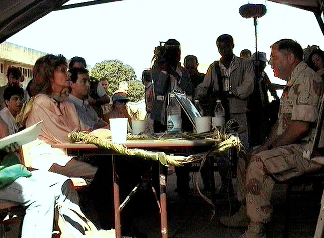 Right side profile of international film star Sophia Loren sitting at a table under a canopy. She visits Joint Task Force Provide Relief facilities at Moi International Airport, Mombasa, Kenya. US Marine BGEN Paul Fratarangelo, Commanding General of Joint Task Force Provide Relief, briefed Ms. Loren, Goodwill Ambassador for the United Nations and High Commissioner for Refugees, on the operation that has been airlifting food into Somalia. Ms. Loren's entourage and members of the media are seen in the background. Provide Relief is in direct support of Operation Restore Hope