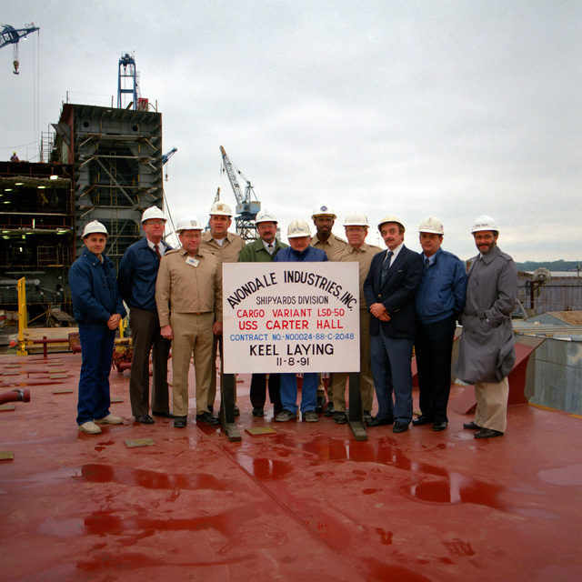 Navy and civilian personnel pose for a photo during the keel laying ceremony for the dock landing ship CARTER HALL (LSD-50) at the Avondale Industries, Inc. (AII) shipyard. They are, from left to right: Kim Ellinburg, AII project engineer; B.J. Griffin, AII project engineer; CPT N.J. Shackelton, director, SUPSHIPS, management group, NAVSEA (SEA071); CPT John C. Donahue, supervisor of shipbuilding, New Orleans (SSNO); Mike Simpson, AII vice president (VP), production; Emile Foret, AII VP, ship construction; LT Ivan Pierce, SSNO, program hull manager; LDR William Dicken, SSNO, program manager's representative; D. Gordon, AII program manager; R. Clark, AII lead production engineer; Carey ...