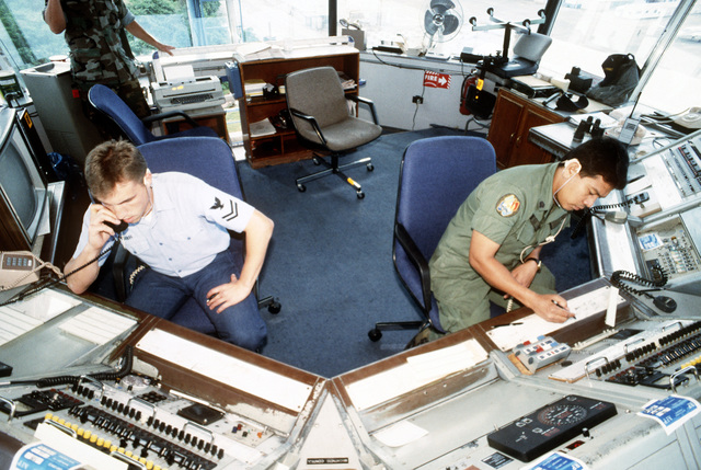 Air controlman 2nd Class John Mahr instructs SSGT Roque Exconde on U.S. Navy air traffic control procedures employed in the air traffic control tower in preparation for transfer of the tower to the Philippine air force. Subic Bay Metropolitan Authority will be assuming control of NAS, Cubi Point and Naval Station, Subic Bay