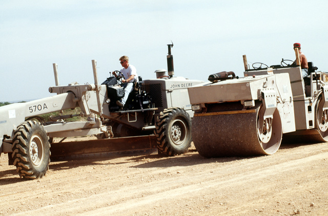 In support of Operation Provide Relief, the 823rd Redhorse Squadron, Hurlburt Field, FL. works to repair airstrips used for relief stops. SSGT Robert Chandler (on grader and in white hat) grades a section of the Hoddur airstrip, as SGT David Dreier uses a vibrating roller to crush and flatten stones on the surface