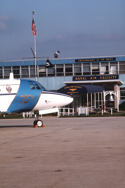 A close-up view of the nose of a CT-39G Sabreliner aircraft parked in front of the terminal building. The aircraft is decorated with the emblems commemorating the 75th anniversary of the Naval Air Reserve