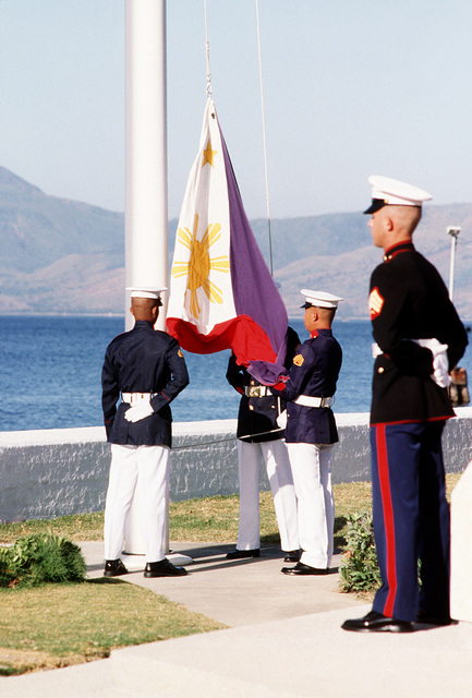 A U.S. Marine stands by as Philippine marines raise their flag over the naval station following the final close-out ceremony. Subic Bay Metropolitan Authority will be assuming control of the facility