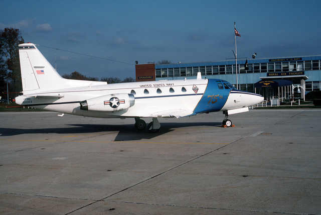 A right side view of a CT-39G Sabreliner aircraft parked in front of the terminal building. The aircraft is decorated with the emblems commemorating the 75th anniversary of the Naval Air Reserve