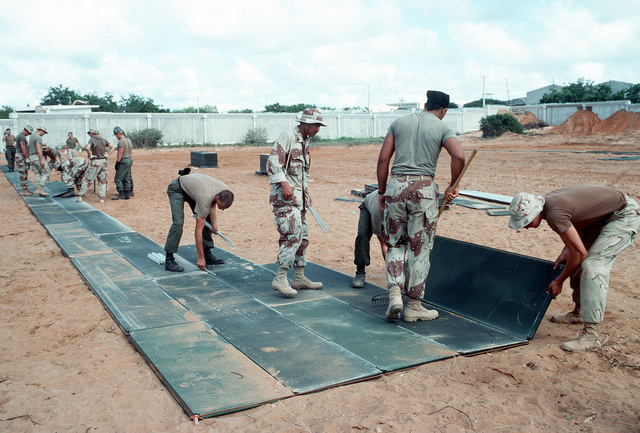 Marines and Seabees work together to build a helicopter landing at the Joint Task Force Somalia headquarters during the multinational relief effort Operation Restore Hope. The headquarters was established at the former U.S. Embassy compound