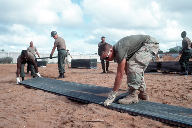 Marines and Seabees work together to build a helicopter landing pad at the Joint Task Force Somalia headquarters during the multinational relief effort Operation Restore Hope. The headquarters was established at the former U.S. Embassy compound