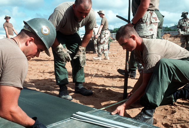 Seabees and Marines work together to build a helicopter landing at the Joint Task Force Somalia headquarters during the multinational relief effort Operation Restore Hope. The headquarters was established at the former U.S. Embassy compound