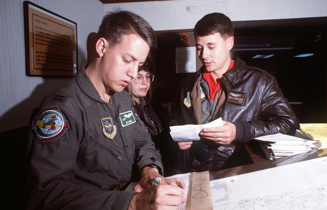 CAPT. James Hawk, a KC-135 Stratotanker pilot from the 310th Air Refueling Squadorn, and CAPT. Tom Swiderek, a Pacific Tanker Task Force flight evaluator from the 18th Wing, plan an upcoming refueling mission in the base operations center