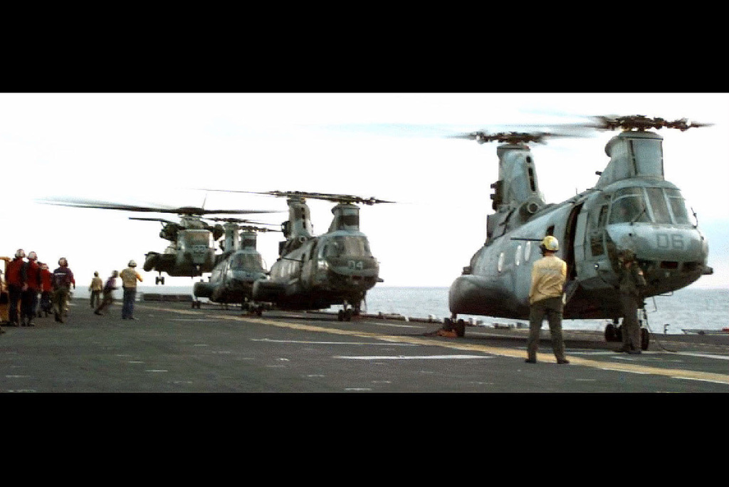 """Four United States Marine Corps helicopters are single file on the flight deck of the Iwo Jima Class Amphibious Assault Ship USS TRIPOLI (LPH 10). From front to back are three CH-46 """"Sea Knight"""" helicopters and one CH-53 """"Super Stallion"""". TRIPOLI flight deck personnel stand on the deck at the left of the frame. The CH-53 hovers a few feet off the deck. This mission is in support of Operation Restore Hope"""