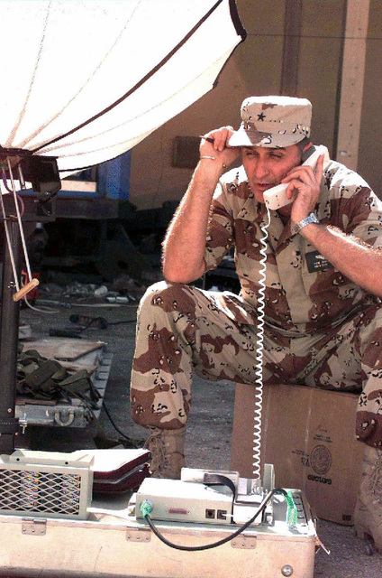Air Force BGEN Thomas Mikolajcik, sits on a cardboard box facing camera, speaks on a telephone handset in preparation and transmission of imagery using IMMARSAT. The general wears desert camouflage BDUs. This mission is in support of Operation Restore Hope