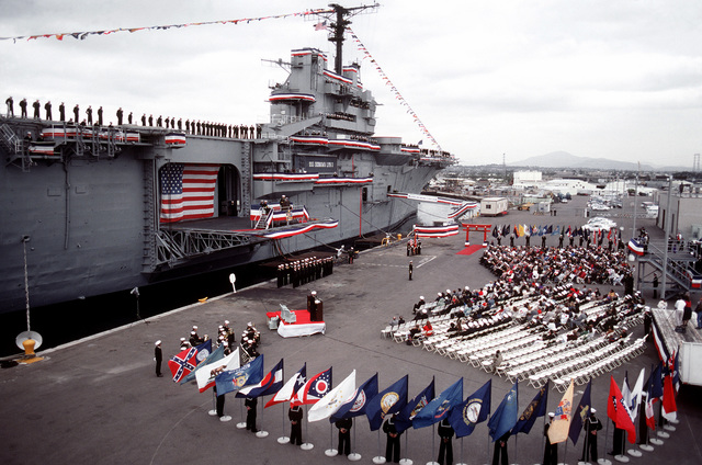 State flags form a semicircle around the audience as an officer speaks during the decommissioning ceremony of the amphibious assault ship USS OKINAWA (LPH-3)