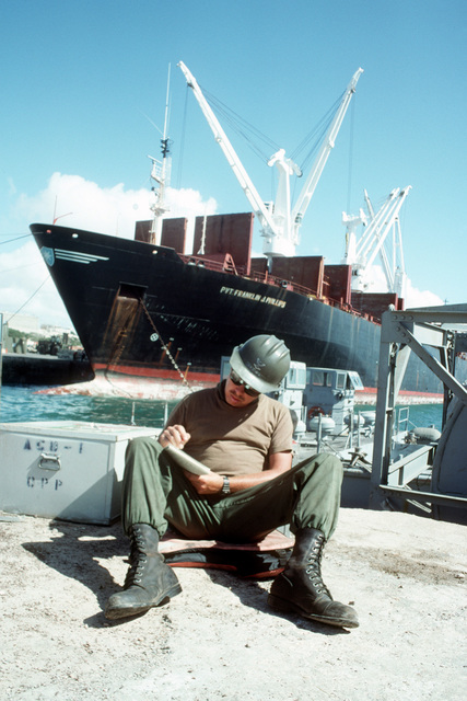 Signalman 3rd Class Rick Mattox, a member of Amphibious Construction Battalion 1, sits in front of the maritime prepositioning ship PVT FRANKLIN J. PHILLIPS (T-AK-3004) while writing a letter during the multinational relief effort OPERATION RESTORE HOPE