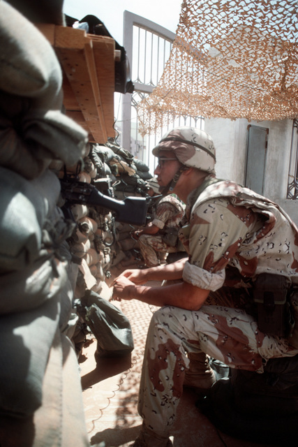 Members of 1ST Platoon, K Company, 3rd Battalion, 9th Marine Regiment, man 5.56mm M-249 squad automatic weapons (SAWs) in the sandbagged bunker at the main gate of the Joint Task Force Somalia headquarters. The headquarters was established at the former U. S. Embassy during OPERATION RESTORE HOPE