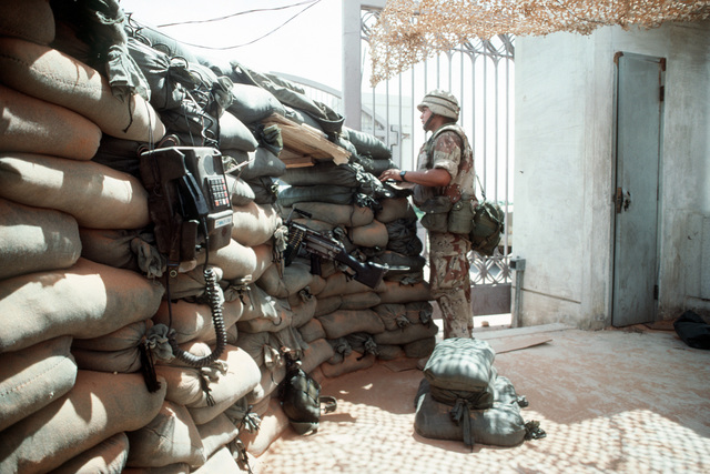 PFC Anthony Mejia, a member of 1ST Platoon, K Company, 3rd Battalion, 9th Marine Regiment, mans a sandbagged bunker at the main gate into the Joint Task Force Somalia headquarters during OPERATION RESTORE HOPE. The headquarters during OPERATION RESTORE HOPE. The headquarters was established in the former U. S. Embassy compound. A 5.56mm M-249 squad automatic weapon (SAV) and a field telephone are in the foreground