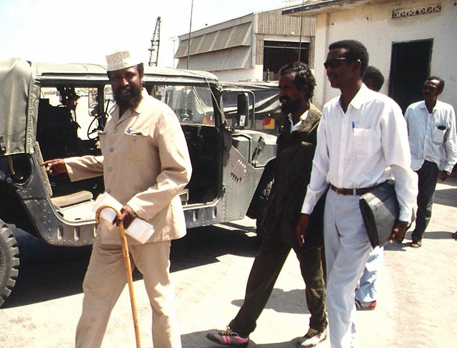 Straight on shot of Somali Faction Leader COL Jess, at left with hat and cane, walking outside the Joint Task Force Headquarters in Kismayo, Somalia with his entourage. He had just completed a meeting with BGEN Lawson Magruder, USA, Joint Task Force Commander in Kismayo. BGEN Magruder, (not shown) is from the 10th Mountain Division Fort Drum, New York. This mission is in direct support of Operation Restore Hope