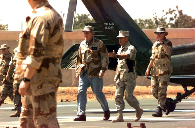 Dressed in a Desert Camouflage BDU Top, US President George Busy walks across the tarmac of Mogadishu Airport from right to left. He is escorted by US Marine LGEN Robert Johnston, Commander, Joint Task Force Operation Restore Hope. This was Bush's New Year's Eve visit to troops deployed to Somalia. Along visiting the troops, Busy also stopped at a food distribution center